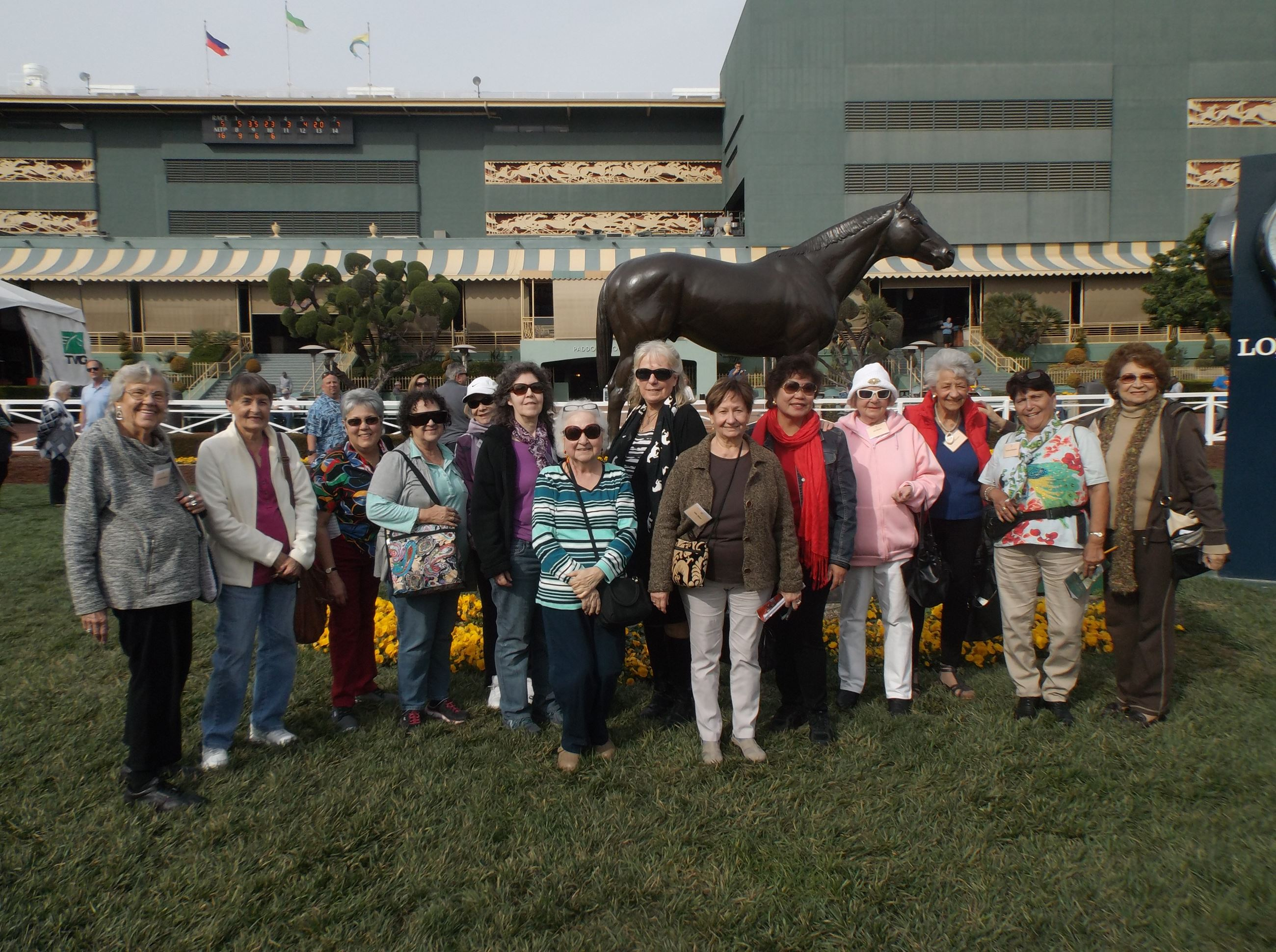 Seniors gathered in front of a horse statue at a fairgrounds